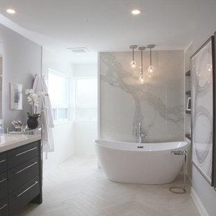 Imagen de cuarto de baño principal, moderno, de tamaño medio, con armarios con paneles lisos, puertas de armario de madera en tonos medios, bañera exenta, ducha abierta, sanitario de una pieza, baldosas y/o azulejos blancos, baldosas y/o azulejos de vidrio laminado, paredes grises, suelo de baldosas de porcelana, lavabo integrado, encimera de cuarcita, suelo beige, ducha abierta y encimeras blancas