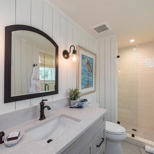 Large beach style 3/4 white tile and subway tile mosaic tile floor and white floor alcove shower photo in Atlanta with shaker cabinets, gray cabinets, a two-piece toilet, white walls, an undermount sink, quartzite countertops, a hinged shower door and gray countertops