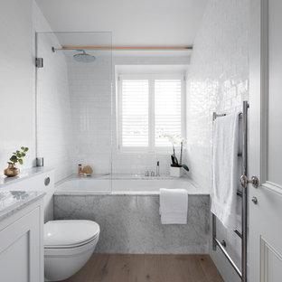 Imagen de cuarto de baño escandinavo con armarios estilo shaker, puertas de armario blancas, combinación de ducha y bañera, sanitario de una pieza, baldosas y/o azulejos de cemento, paredes blancas, suelo de madera clara, suelo beige y ducha abierta