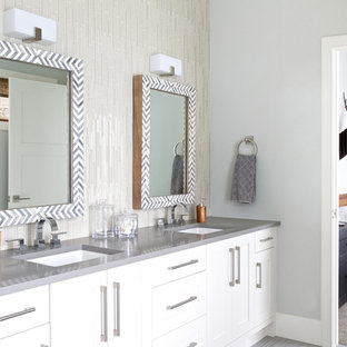 Inspiration for a large transitional master bathroom in Calgary with shaker cabinets, white cabinets, a drop-in tub, grey walls, porcelain floors, an undermount sink, solid surface benchtops and grey floor.