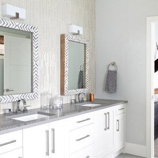 Immagine di una grande stanza da bagno padronale chic con ante in stile shaker, ante bianche, vasca da incasso, pareti grigie, pavimento in gres porcellanato, lavabo sottopiano, top in superficie solida e pavimento grigio