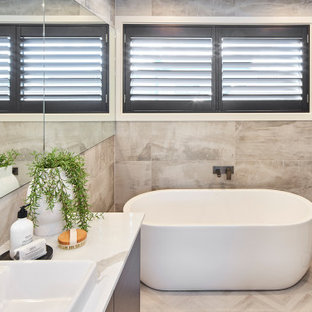 This is an example of a mid-sized contemporary master bathroom in Other with flat-panel cabinets, dark wood cabinets, a freestanding tub, a corner shower, gray tile, porcelain tile, a vessel sink, grey floor, a hinged shower door, white benchtops and a built-in vanity.