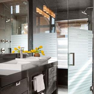 Diseño de cuarto de baño actual con lavabo sobreencimera, armarios tipo mueble, puertas de armario negras, encimera de cuarcita, ducha a ras de suelo, baldosas y/o azulejos grises y baldosas y/o azulejos de porcelana