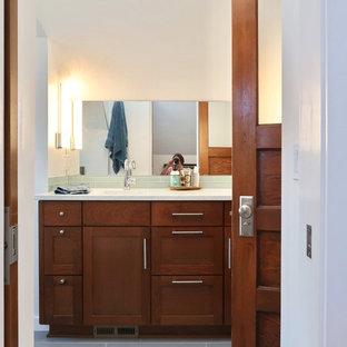 Modelo de cuarto de baño principal, de estilo americano, de tamaño medio, con armarios estilo shaker, puertas de armario de madera oscura, bañera empotrada, combinación de ducha y bañera, sanitario de pared, baldosas y/o azulejos azules, baldosas y/o azulejos de vidrio, paredes blancas, suelo de baldosas de cerámica, lavabo bajoencimera, encimera de cuarzo compacto, suelo gris y ducha con puerta con bisagras