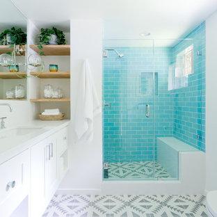Foto de cuarto de baño de tamaño medio con armarios estilo shaker, puertas de armario blancas, baldosas y/o azulejos azules, baldosas y/o azulejos de cerámica, paredes blancas, suelo de azulejos de cemento, lavabo encastrado, encimera de cuarzo compacto, suelo gris y ducha con puerta con bisagras