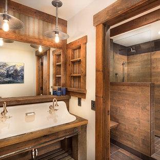 Foto de cuarto de baño infantil, rústico, de tamaño medio, con armarios abiertos, puertas de armario de madera oscura, ducha empotrada, sanitario de pared, baldosas y/o azulejos marrones, baldosas y/o azulejos de porcelana, paredes beige, suelo de madera en tonos medios, lavabo suspendido y encimera de madera