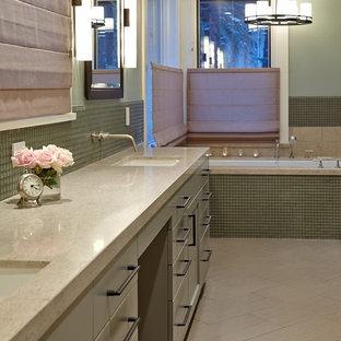 Ispirazione per una grande stanza da bagno padronale minimal con ante lisce, ante verdi, vasca sottopiano, doccia ad angolo, piastrelle beige, pareti verdi, pavimento in gres porcellanato, lavabo sottopiano e top in pietra calcarea