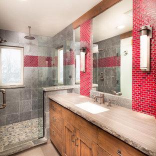 Modelo de cuarto de baño infantil, rústico, de tamaño medio, con armarios tipo mueble, puertas de armario de madera oscura, ducha abierta, baldosas y/o azulejos rojos, lavabo bajoencimera, encimera de mármol y paredes multicolor