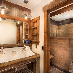 Foto på ett mellanstort rustikt brun en-suite badrum, med öppna hyllor, skåp i slitet trä, brun kakel, porslinskakel, beige väggar, ett avlångt handfat, träbänkskiva, en öppen dusch, klinkergolv i porslin och med dusch som är öppen