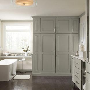 Foto de cuarto de baño principal, contemporáneo, de tamaño medio, con lavabo tipo consola, armarios con paneles lisos, puertas de armario beige, encimera de ónix, bañera exenta, paredes blancas y suelo de madera oscura
