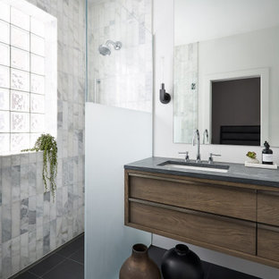 Mid-sized trendy master white tile and marble tile slate floor and black floor walk-in shower photo in Chicago with flat-panel cabinets, medium tone wood cabinets, white walls, an undermount sink, limestone countertops, a hinged shower door and gray countertops