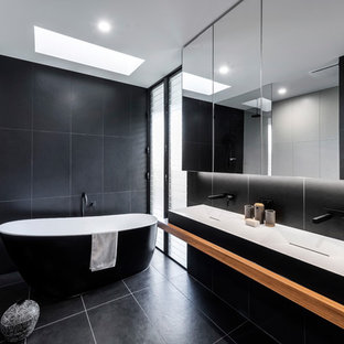 Design ideas for a contemporary bathroom in Gold Coast - Tweed with a freestanding tub, black tile, a vessel sink, wood benchtops, black floor and brown benchtops.