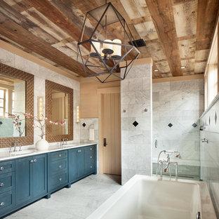Modelo de cuarto de baño rústico con armarios con paneles lisos, puertas de armario azules, bañera exenta, ducha esquinera, baldosas y/o azulejos blancos, baldosas y/o azulejos de mármol, lavabo bajoencimera, encimera de mármol, ducha abierta y encimeras blancas