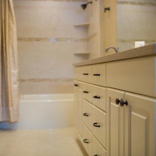 Modelo de cuarto de baño principal, tradicional, de tamaño medio, con armarios con paneles con relieve, puertas de armario blancas, bañera empotrada, combinación de ducha y bañera, sanitario de dos piezas, paredes beige, lavabo bajoencimera, encimera de terrazo y ducha con cortina