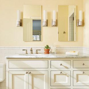 Exemple d'une salle de bain chic avec un placard avec porte à panneau encastré, des portes de placard beiges, un carrelage blanc, un carrelage métro, un mur jaune, un lavabo encastré, un plan de toilette gris et un plan de toilette en marbre.