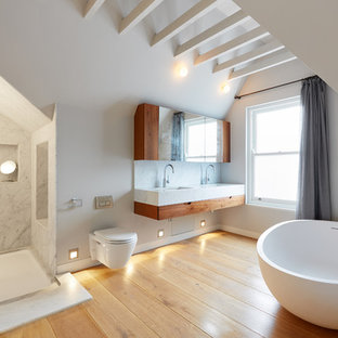 Large modern bathroom in London with flat-panel cabinets, brown cabinets, a freestanding bath, a wall mounted toilet, white walls, light hardwood flooring, a wall-mounted sink, marble worktops, beige floors, an open shower and grey worktops.