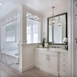 Inspiration for a mid-sized beach style master white tile and marble tile porcelain floor and gray floor alcove shower remodel in Orange County with white cabinets, marble countertops, white walls, an undermount sink, an undermount tub, recessed-panel cabinets and a hinged shower door