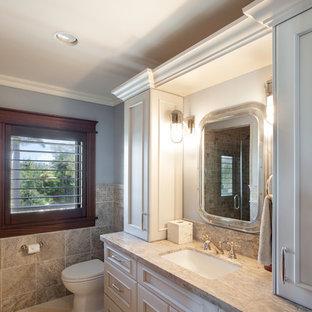 Ispirazione per un'ampia stanza da bagno con doccia tropicale con ante bianche, piastrelle beige, pareti blu, ante con riquadro incassato, WC a due pezzi, piastrelle in travertino, pavimento in marmo, lavabo da incasso, top in granito e pavimento beige