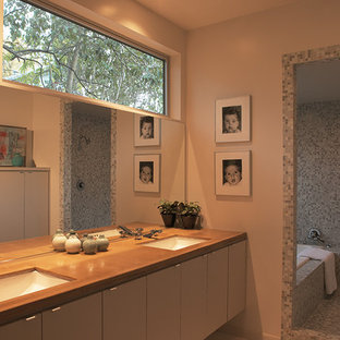 Mid-sized midcentury modern master mirror tile mosaic tile floor bathroom photo in Austin with flat-panel cabinets, white cabinets, beige walls, an undermount sink and wood countertops