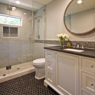 Diseño de cuarto de baño principal, clásico, de tamaño medio, con armarios con paneles empotrados, puertas de armario blancas, ducha empotrada, baldosas y/o azulejos grises, baldosas y/o azulejos de mármol, paredes grises, lavabo bajoencimera, encimera de esteatita, ducha con puerta con bisagras, suelo de baldosas de porcelana y suelo negro