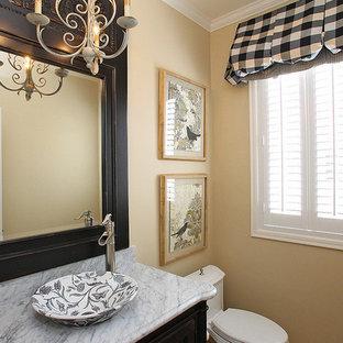 Foto de cuarto de baño con ducha, clásico, con lavabo sobreencimera, armarios tipo mueble, puertas de armario negras, encimera de ónix, sanitario de una pieza, paredes beige y suelo de madera en tonos medios