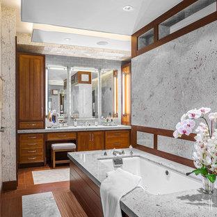 ボストンの広いコンテンポラリースタイルのおしゃれなマスターバスルーム (落し込みパネル扉のキャビネット、中間色木目調キャビネット、御影石の洗面台、アンダーマウント型浴槽、アンダーカウンター洗面器、グレーの壁、無垢フローリング、茶色い床) の写真