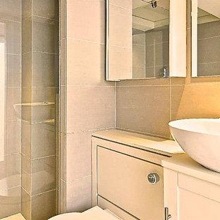 Ispirazione per una piccola stanza da bagno con doccia design con doccia aperta, WC sospeso, piastrelle beige, piastrelle in ceramica, pavimento in pietra calcarea e lavabo a consolle