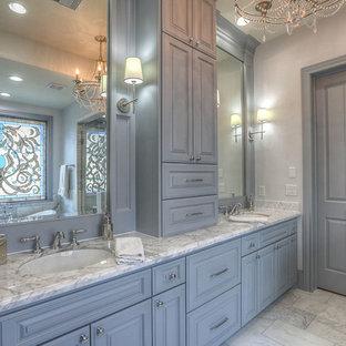 Foto di una grande stanza da bagno padronale classica con ante con bugna sagomata, ante grigie, vasca con piedi a zampa di leone, doccia ad angolo, piastrelle bianche, piastrelle di marmo, pareti bianche, pavimento in marmo, lavabo sottopiano e top in marmo