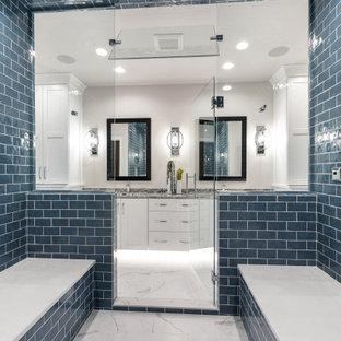 他の地域の広いトランジショナルスタイルのおしゃれなマスターバスルーム (シェーカースタイル扉のキャビネット、黄色いキャビネット、分離型トイレ、青いタイル、サブウェイタイル、白い壁、磁器タイルの床、アンダーカウンター洗面器、御影石の洗面台、白い床、開き戸のシャワー、マルチカラーの洗面カウンター、シャワーベンチ、洗面台2つ、造り付け洗面台) の写真