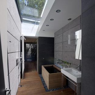 Immagine di una piccola stanza da bagno moderna con vasca giapponese, pavimento in legno massello medio, doccia a filo pavimento e lavabo a consolle