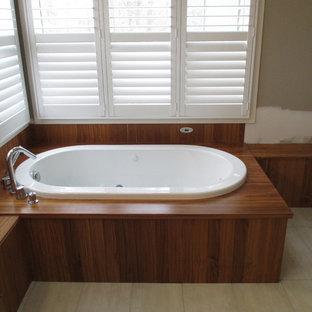 Idee per una stanza da bagno padronale etnica di medie dimensioni con ante lisce, ante in legno scuro, vasca da incasso, pareti verdi, pavimento in gres porcellanato, lavabo a bacinella e top in legno