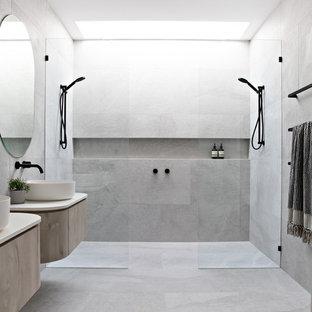 Идея дизайна: ванная комната в современном стиле с плоскими фасадами, светлыми деревянными фасадами, серой плиткой, настольной раковиной, серым полом, открытым душем, бежевой столешницей и двойным душем