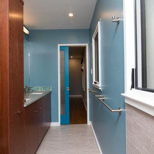Modelo de cuarto de baño principal, retro, de tamaño medio, con armarios con paneles lisos, puertas de armario de madera en tonos medios, ducha abierta, sanitario de dos piezas, baldosas y/o azulejos azules, baldosas y/o azulejos de vidrio laminado, paredes azules, suelo de baldosas de porcelana, lavabo bajoencimera, encimera de vidrio reciclado, suelo gris, ducha abierta y encimeras grises