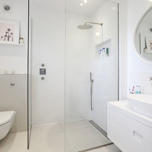 Photo of a small contemporary shower room in London with flat-panel cabinets, a wall mounted toilet, white tiles, white walls, a vessel sink, beige floors, an open shower, white cabinets and a walk-in shower.