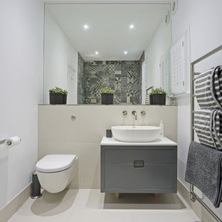 This is an example of a medium sized contemporary shower room bathroom in London with flat-panel cabinets, grey cabinets, a wall mounted toilet, white walls, a vessel sink, beige floors and white worktops.