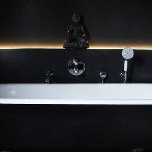 Diseño de cuarto de baño infantil, romántico, de tamaño medio, con lavabo suspendido, armarios con paneles lisos, puertas de armario negras, bañera con patas, ducha abierta, sanitario de pared, baldosas y/o azulejos negros, paredes negras y suelo de baldosas de porcelana