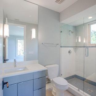 Ejemplo de cuarto de baño infantil, actual, pequeño, con armarios con paneles lisos, puertas de armario azules, ducha empotrada, sanitario de dos piezas, baldosas y/o azulejos beige, baldosas y/o azulejos azules, baldosas y/o azulejos grises, baldosas y/o azulejos de porcelana, paredes grises, suelo de baldosas de porcelana, lavabo bajoencimera y encimera de piedra caliza