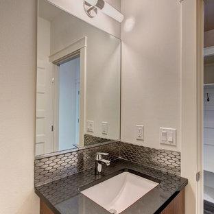 Удачное сочетание для дизайна помещения: маленькая ванная комната в стиле модернизм с плоскими фасадами, светлыми деревянными фасадами, ванной в нише, раздельным унитазом, черной плиткой, металлической плиткой, белыми стенами, полом из керамогранита, врезной раковиной, столешницей из искусственного кварца и серым полом - самое интересное для вас