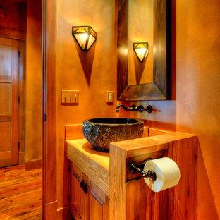 Modelo de cuarto de baño con ducha, de estilo de casa de campo, de tamaño medio, con armarios con paneles con relieve, puertas de armario de madera oscura, sanitario de una pieza, paredes beige, suelo de madera en tonos medios, lavabo sobreencimera, encimera de madera, suelo marrón y encimeras marrones