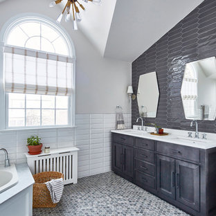 Example of a mid-sized transitional master white tile, gray tile and ceramic tile gray floor corner bathtub design in New York with gray cabinets, gray walls, engineered quartz countertops, shaker cabinets, an undermount sink and white countertops