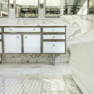 Modelo de cuarto de baño principal, contemporáneo, grande, con lavabo bajoencimera, armarios tipo mueble, puertas de armario blancas, encimera de mármol, bañera exenta, ducha empotrada, baldosas y/o azulejos blancos, baldosas y/o azulejos con efecto espejo, paredes blancas y suelo con mosaicos de baldosas