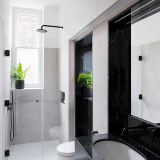 Medium sized contemporary shower room bathroom in London with an alcove shower, a wall mounted toilet, grey tiles, ceramic tiles, ceramic flooring, a submerged sink, granite worktops, a hinged door, black worktops, flat-panel cabinets, black cabinets and grey floors.