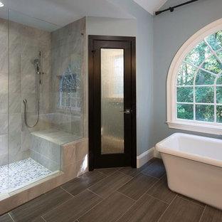 Diseño de cuarto de baño principal, asiático, grande, con armarios abiertos, puertas de armario de madera clara, bañera exenta, ducha doble, baldosas y/o azulejos grises, baldosas y/o azulejos de porcelana, paredes azules, suelo de baldosas de porcelana, lavabo sobreencimera, encimera de cuarzo compacto, suelo gris y ducha con puerta con bisagras