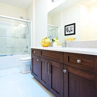 バンクーバーの中サイズのトランジショナルスタイルのおしゃれな子供用バスルーム (シェーカースタイル扉のキャビネット、濃色木目調キャビネット、アルコーブ型浴槽、シャワー付き浴槽、グレーのタイル、メタルタイル、ベージュの壁、大理石の床、アンダーカウンター洗面器、珪岩の洗面台) の写真