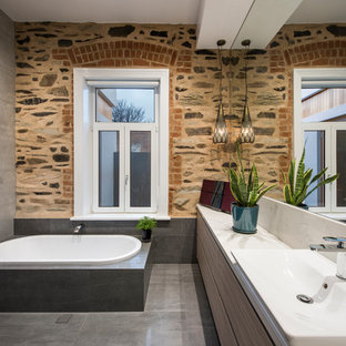 Design ideas for a contemporary bathroom in Adelaide with flat-panel cabinets, light wood cabinets, a drop-in tub, gray tile, a vessel sink and grey floor.