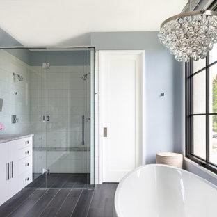 Пример оригинального дизайна: главная ванная комната среднего размера в современном стиле с фасадами островного типа, белыми фасадами, отдельно стоящей ванной, душем без бортиков, белой плиткой, синими стенами, полом из керамогранита, врезной раковиной, столешницей из оникса, серым полом, душем с распашными дверями, серой столешницей и керамогранитной плиткой