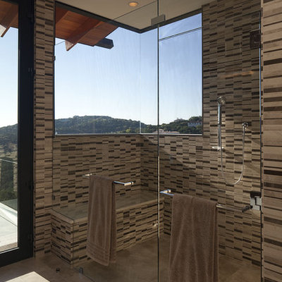 Large trendy master beige tile and stone tile porcelain tile bathroom photo in Austin with flat-panel cabinets, medium tone wood cabinets, brown walls, an undermount sink and solid surface countertops