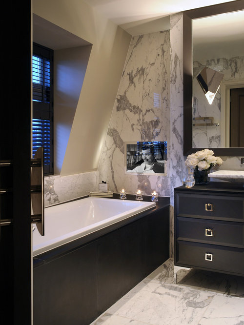 tv in bathroom. trendy marble floor drop-in bathtub photo in london with a vessel sink, furniture tv bathroom