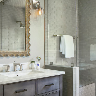 Example of a small farmhouse 3/4 gray tile and glass tile limestone floor and gray floor alcove shower design in Austin with flat-panel cabinets, gray cabinets, a one-piece toilet, gray walls, a drop-in sink, marble countertops, a hinged shower door and white countertops