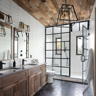 Inspiration for a transitional 3/4 white tile black floor alcove shower remodel in Denver with shaker cabinets, medium tone wood cabinets, an undermount sink, a hinged shower door and gray countertops